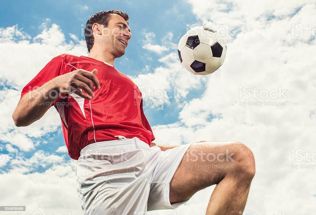 Smiling soccer player practicing with ball against the sky. stock photo