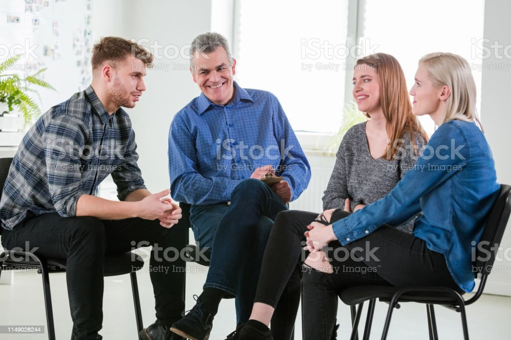 Smiling social worker with students during therapy Smiling mental health therapist and female students looking at male during meeting. Young man and women are sitting with social worker in lecture hall. They are in university during group therapy. 18-19 Years Stock Photo