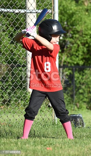 6 year old girl batting in her first softball game, smiling, springtime Naperville, Illinios  USA