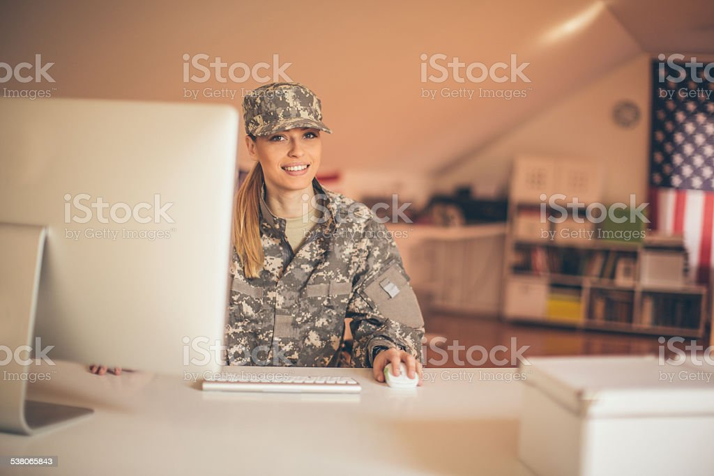 Smiling soldier using computer stock photo