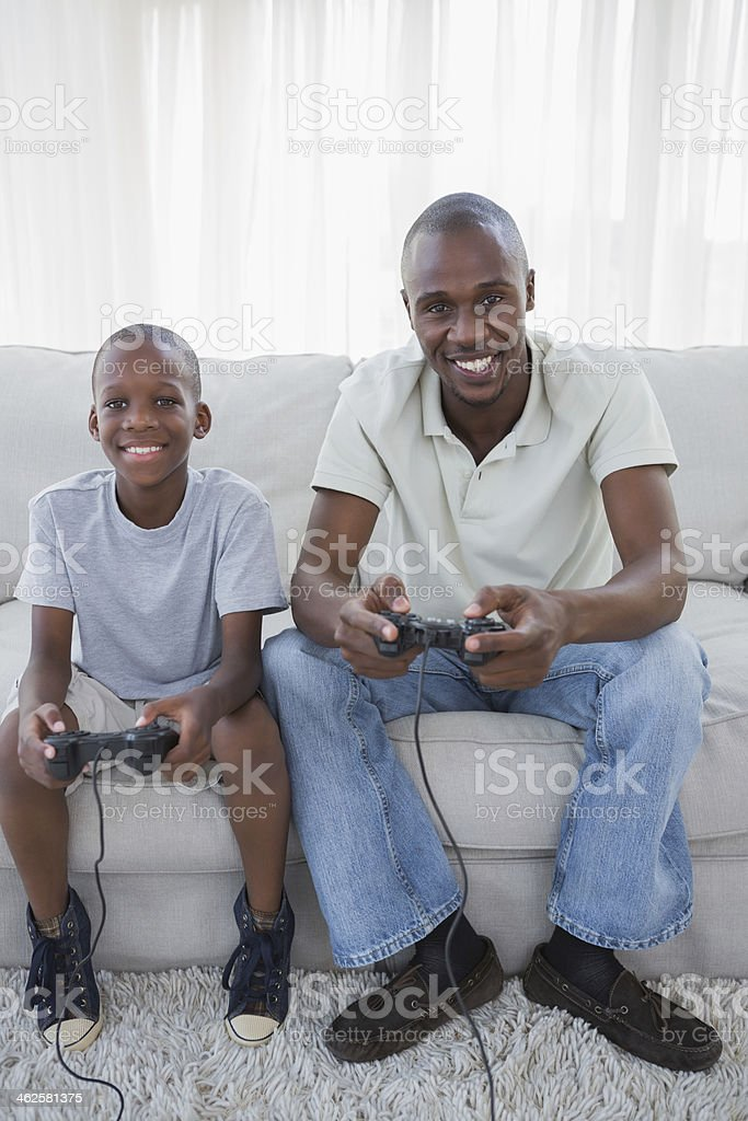 Smiling son and father playing video games together royalty-free stock photo