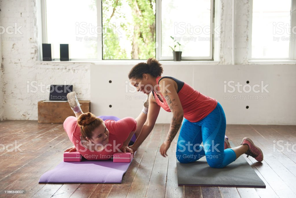 Afro American lady helping Caucasian fat woman to do push-ups...