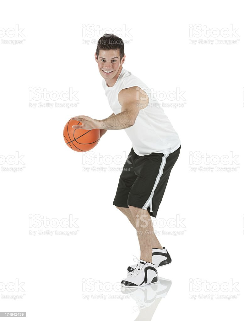 Smiling sportsman playing with a basketball royalty-free stock photo