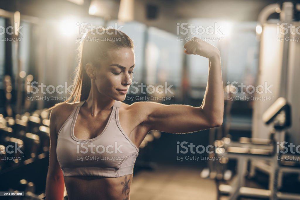 Smiling sportswoman flexing her muscles in a health club. royalty-free stock photo