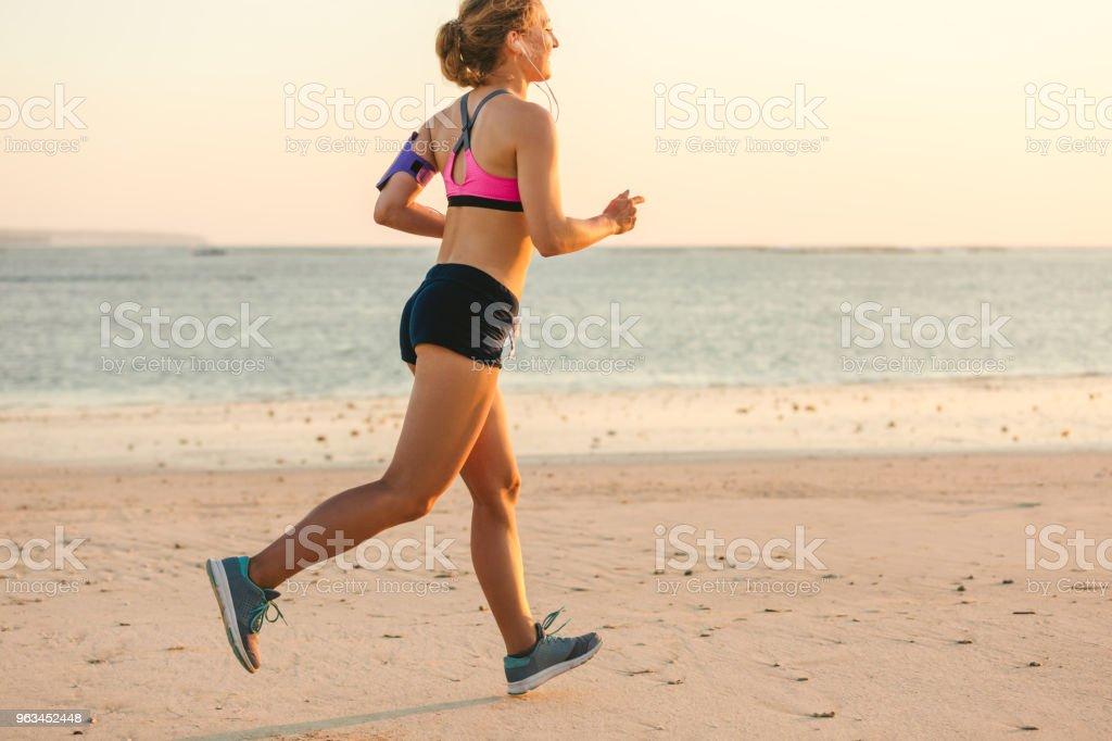 Kulaklıklar içinde gülümseyen sporcumuz deniz ile sahilde koşu omuz çantası çalıştıran smartphone ile - Royalty-free Aktivite Stok görsel