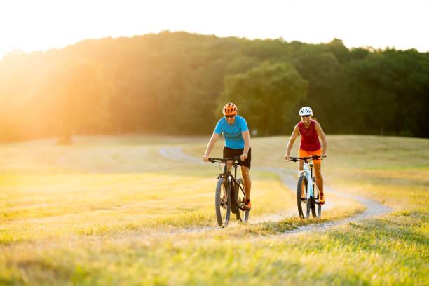 lächelnde sportliches Paar auf Mountain-Bikes in ländlichen Landschaft – Foto