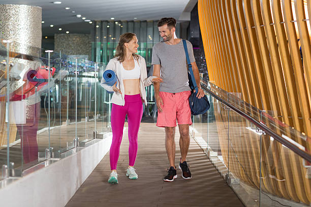 smiling sporty couple walking and chatting - bh träger stock-fotos und bilder
