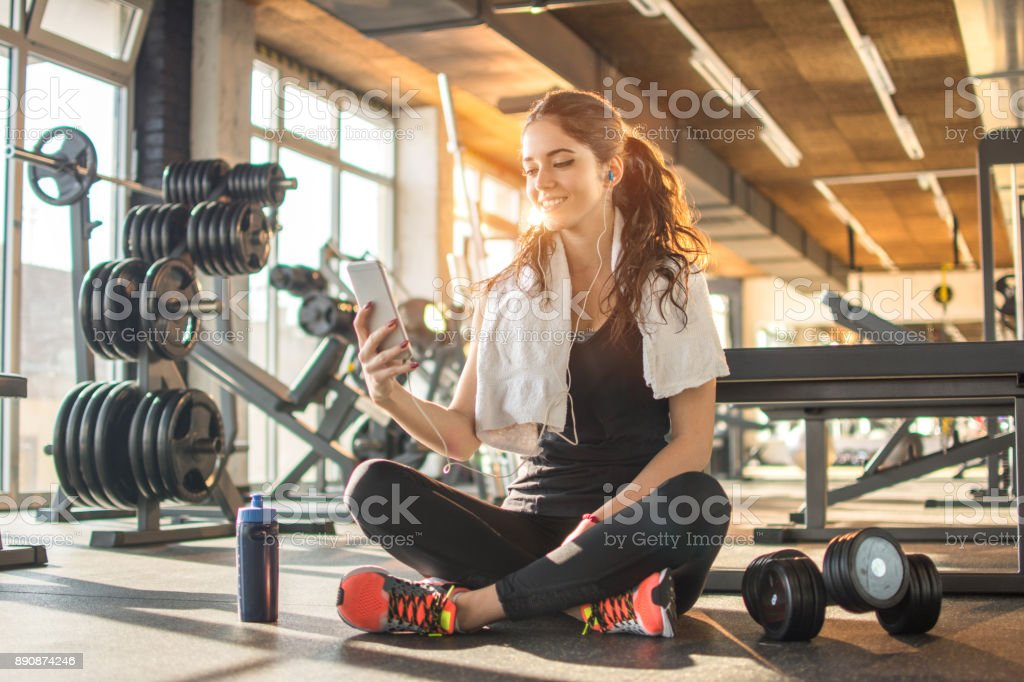 Smiling sporty girl with earphones using phone while sitting down on floor after hard workout in the gym. stock photo