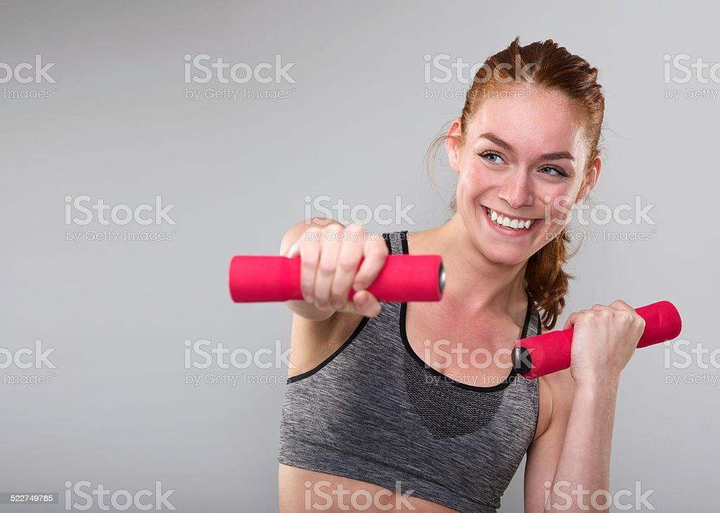 Smiling sporty woman exercising with weights stock photo