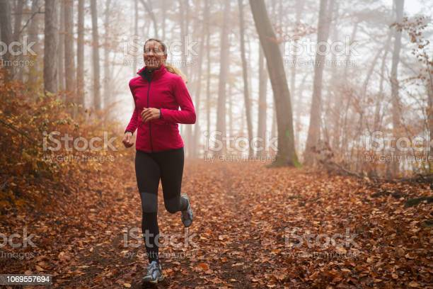 Photo of smiling sporty woman jogging alone through misty forest in autumn