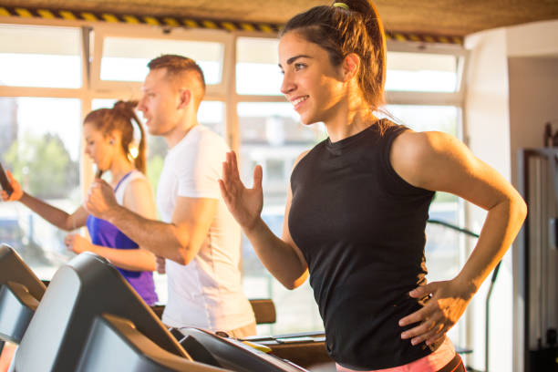 Smiling sporty woman running on a treadmill in gym. stock photo