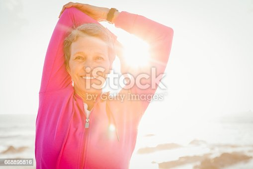 istock Smiling sporty woman stretching arms at promenade 668895816