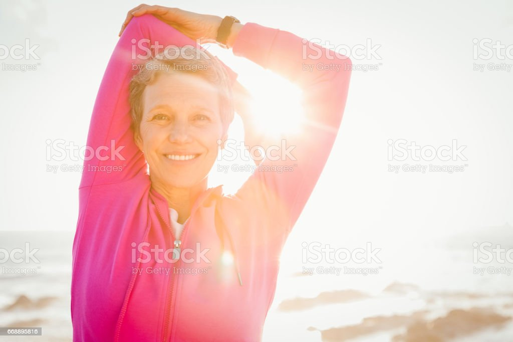 Smiling sporty woman stretching arms at promenade - foto stock