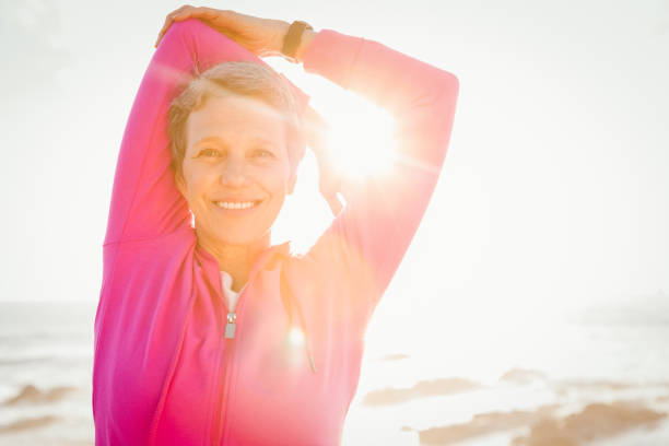Smiling sporty woman stretching arms at promenade Portrait of smiling sporty woman stretching arms at promenade on a sunny day one mature woman only stock pictures, royalty-free photos & images