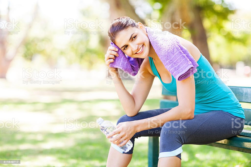 Smiling Sporty Woman Wiping Sweat On Park Bench stock photo