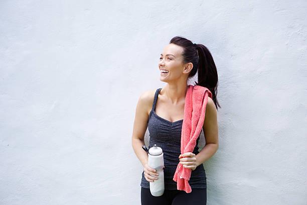 lächelnd, sportliche frau mit flasche wasser und handtuch - rosa training stock-fotos und bilder