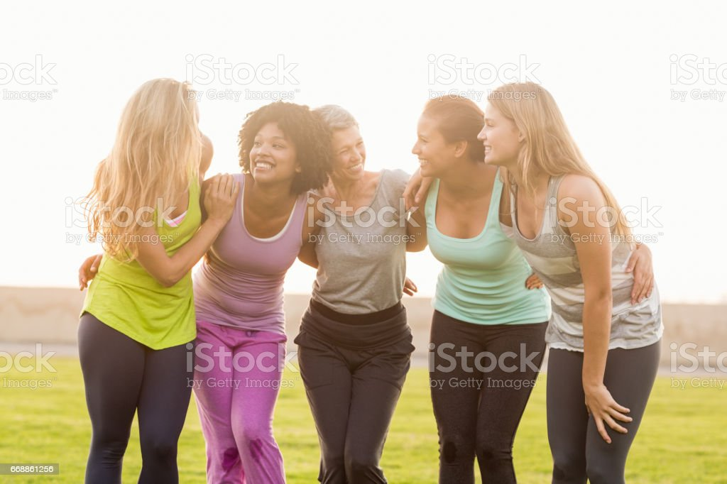 Smiling sporty women with arms around each other stock photo