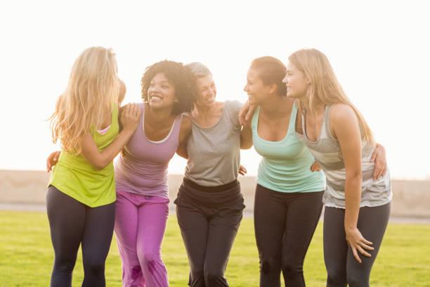 sportieve vrouwen met armen om elkaar heen glimlachen - 30 39 jaar stockfoto's en -beelden