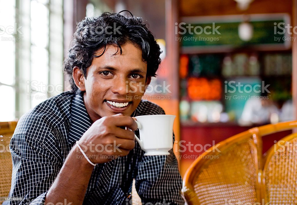 Smiling Sri Lankan young man drinking tea in a shop. stock photo