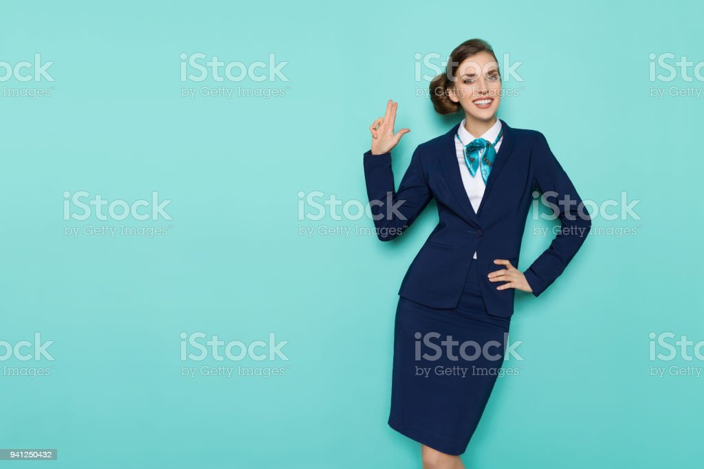 Smiling Stewardess Is Showing Pistol Hand Sign stock photo