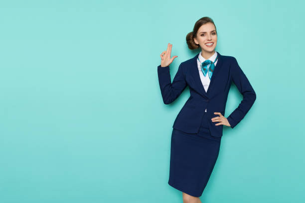 Smiling Stewardess Is Showing Pistol Hand Sign Happy stewardess in blue formal wear is showing pistol hand sign, smiling and looking at camera. Three quarter length studio shot on turquoise background. cabin crew stock pictures, royalty-free photos & images