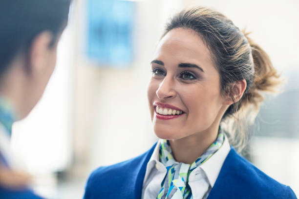 Smiling stewardess looking at coworker in airport stock photo