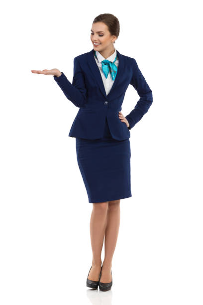 Smiling Stewardess Presenting And Watching Smiling young businesswoman in blue formalwear and high heels is standing with hand raised and looking away. Front view. Full length studio shot isolated on white. air stewardess stock pictures, royalty-free photos & images