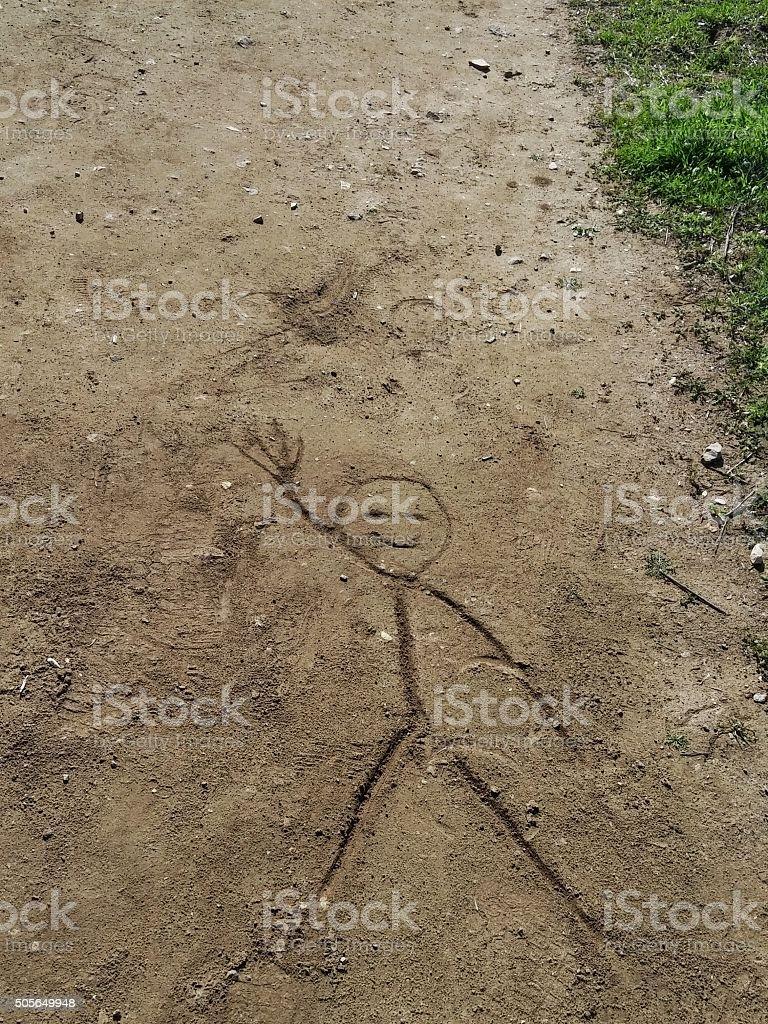 Souriant personnage bâton personne agitant dessin dans la saleté chemin Road - Photo