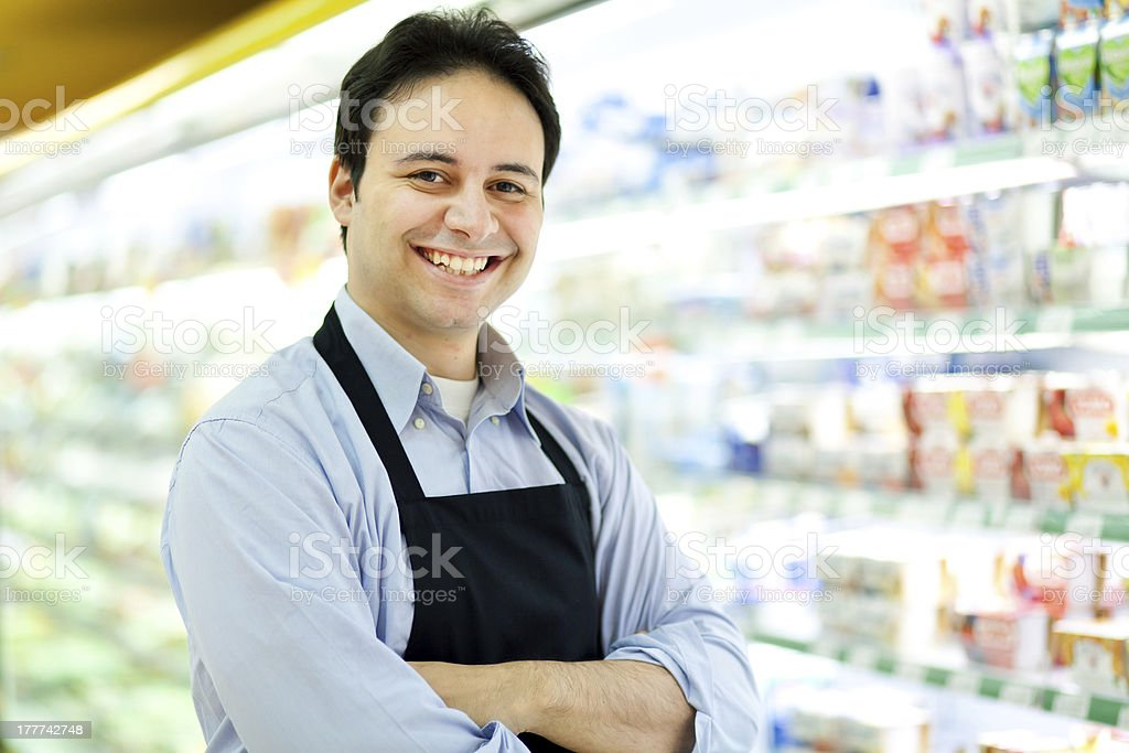 Smiling store keeper in his supermarket stock photo