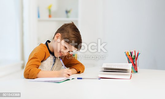 istock smiling student boy writing to notebook at home 501543368