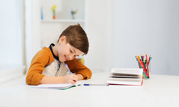 smiling student boy writing to notebook at home stock photo