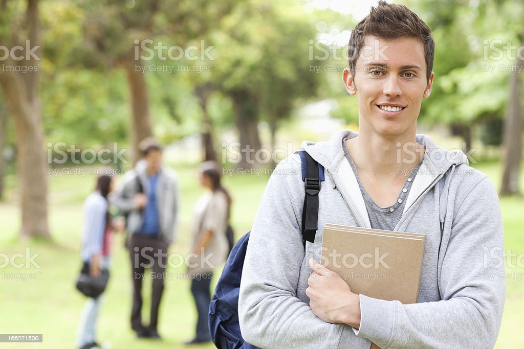 Smiling student crossing his arms with friends in background royalty-free stock photo