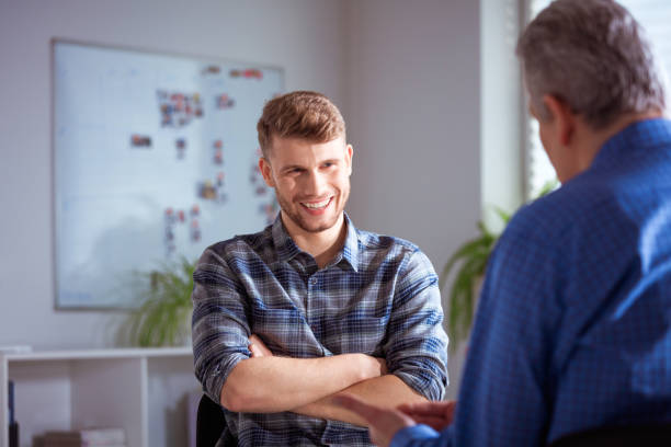 Smiling student discussing with male therapist Smiling young student talking to therapist. Man is discussing with mature mental health professional. They are wearing casuals in lecture hall at university. alternative therapy stock pictures, royalty-free photos & images