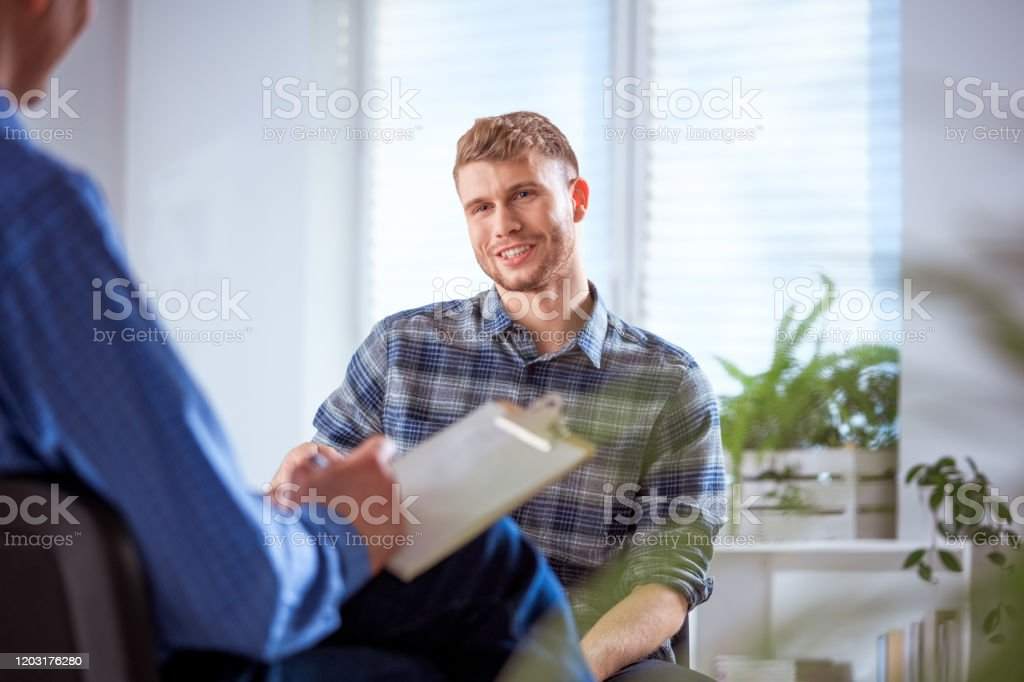 Smiling student discussing with male therapist Smiling young student talking to therapist. Man is discussing with mental health professional. They are sitting in lecture hall at university. 20-24 Years Stock Photo