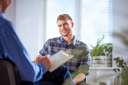 Smiling Student Discussing With Male Therapist Stock Photo - Download Image Now