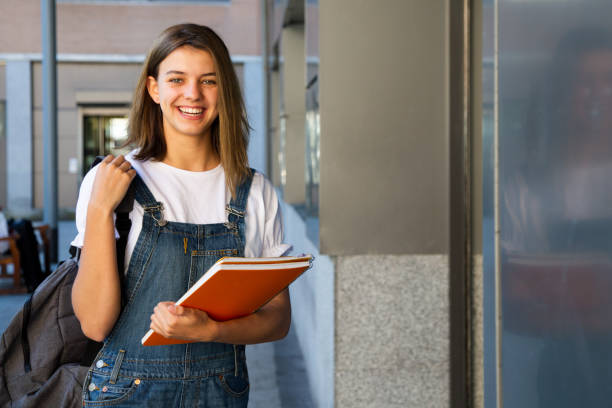 Smiling student girl at the school entrance stock photo