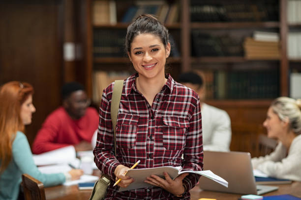 Smiling student girl in library stock photo