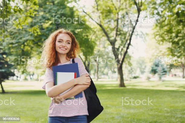 微笑的學生女孩與書在室外公園 照片檔及更多 一個人 照片