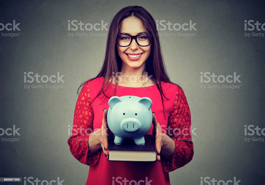 Smiling student, happy woman, holding books and piggy bank in hands stock photo