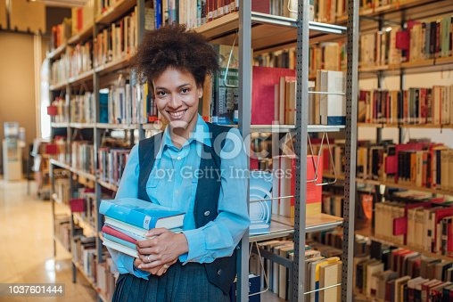 istock Smiling student holding books 1037601444