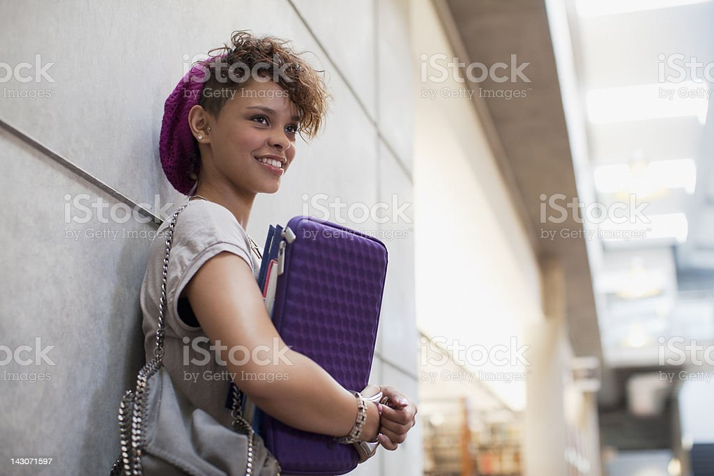 Smiling student leaning against wall stock photo