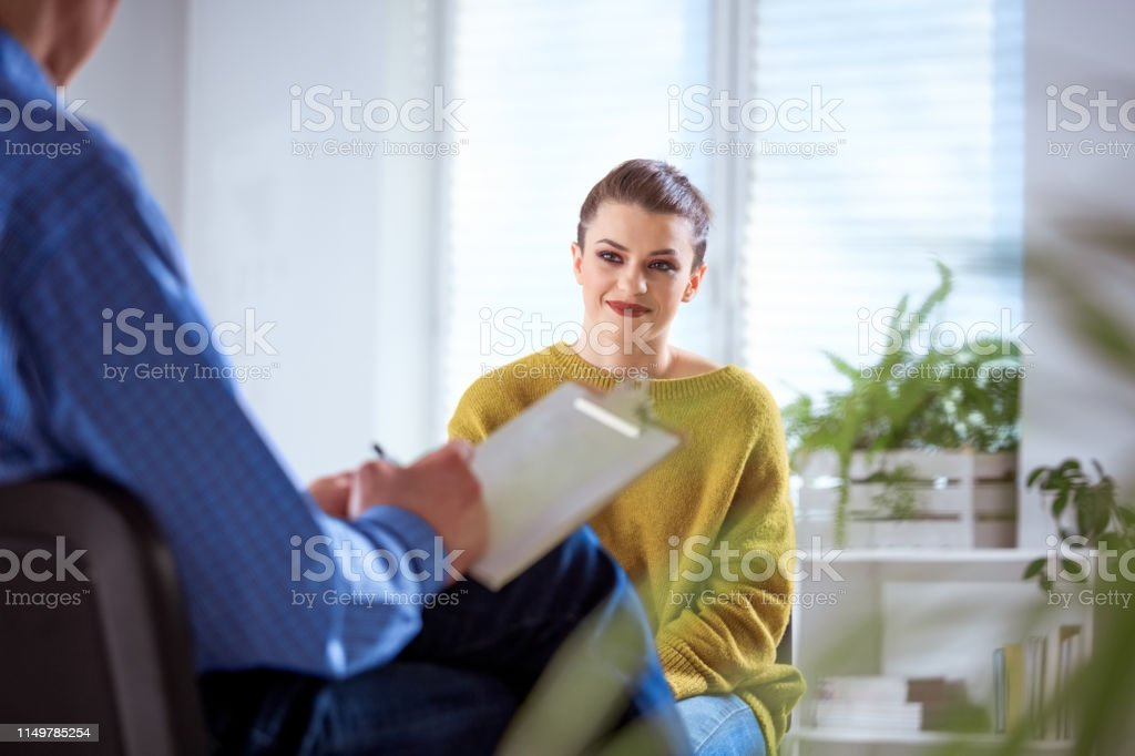 Smiling student listening to mature therapist Smiling woman listening to male therapist in meeting. Female university student is discussing with mental health professional. They are sitting in lecture hall during session. 18-19 Years Stock Photo