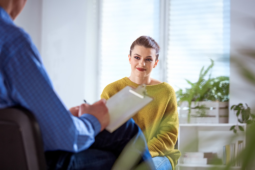 Smiling Student Listening To Mature Therapist Stock Photo - Download Image Now