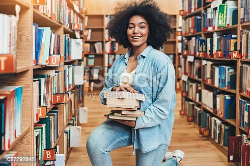 istock Smiling student picking books in the library 1087792842