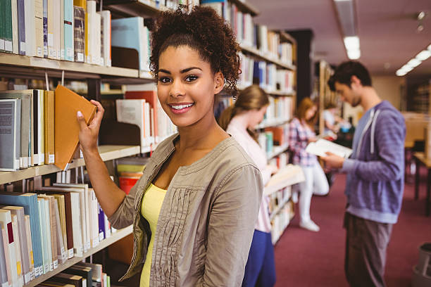 Smiling student picking out a book stock photo