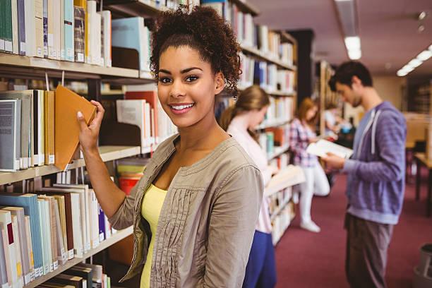 lächelnd student such dir ein buch - öffentliches gebäude stock-fotos und bilder