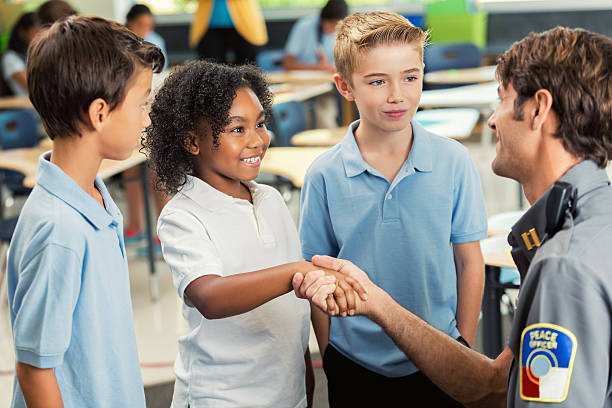 Smiling student shakes hands with police officer Cute African American student smiles while shaking hands with visiting police officer. He is talking to them about safety concerns. They are wearing school uniforms. Students are studying in the background. police meeting stock pictures, royalty-free photos & images