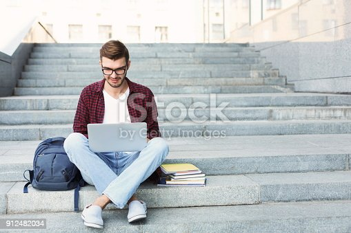 Smiling student sitting on stairs working with laptop, preparing for exams outdoors, having rest in university campus. Technology, education and remote working concept, copy space