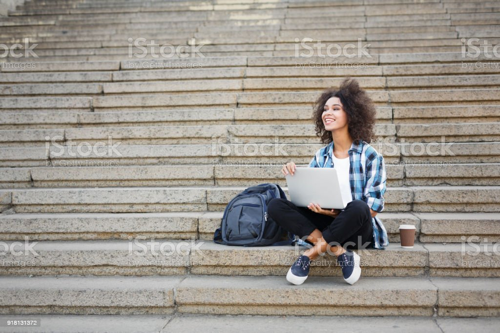 Smiling student sitting on stairs using laptop stock photo
