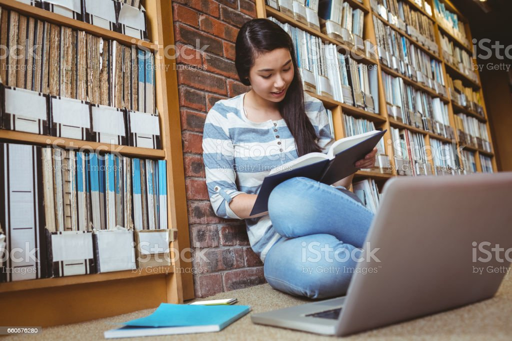 Smiling student sitting on the floor against wall in library studying with laptop and books royalty-free stock photo